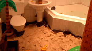A small bathroom filled with sand; there's a plastic bucket and spade in the sand, a treasure chest, and several large inflatable palm trees